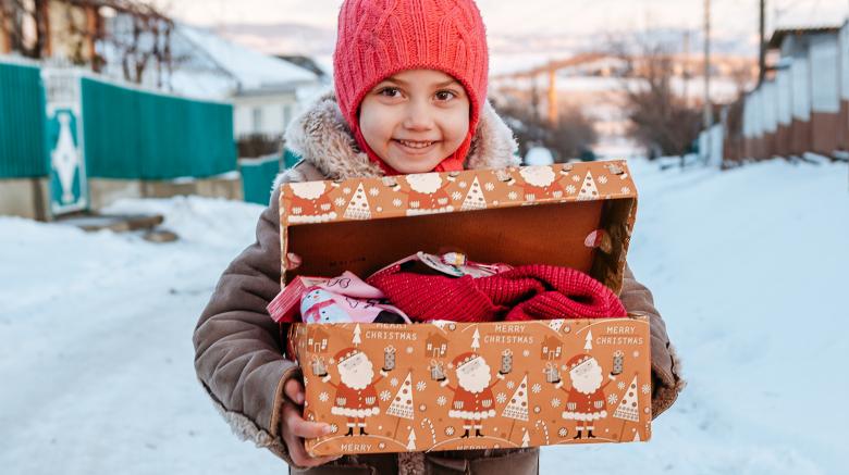Mädchen mit Karton von Weihnachten im Schuhkarton