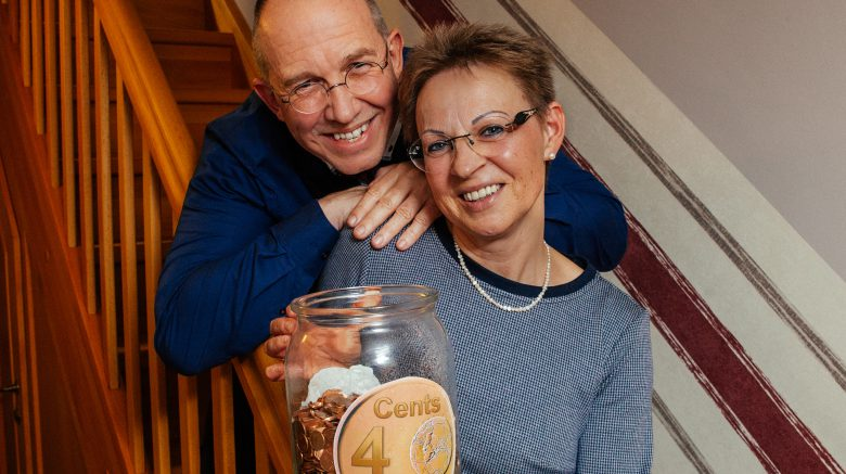 Klaus Matthießen und Ulrike Matthießen stehen auf einer Treppe und halten ein Glas mit Spenden Cents von der Spendenaktion Cents4Children in der Hand