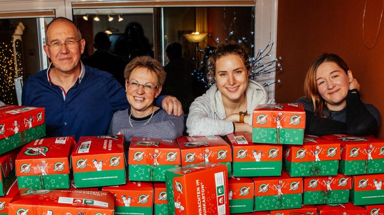 Das Team von der Spendenaktion Cents4Children Klaus Matthießen, Ulrike Matthießen, Adeline Block und Anita Benke stehen vor einem Tisch mit vielen Geschenken für Weihnachten im Schuhkarton von Samaritans Purse